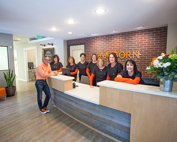 Dr. Reid Amborn and the staff at Amborn Othodontics wearing orange and smiling at the front desk