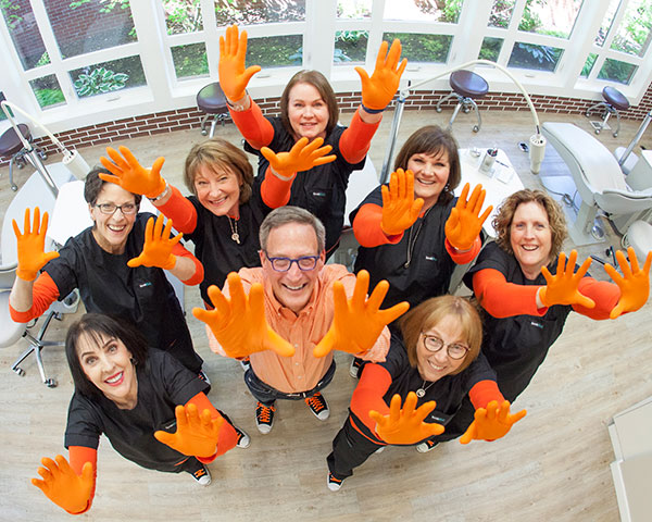 Reid Amborn, DMD and his Salem, OR orthodontic team at Amborn Orthodontics raising their hands and smiling.
