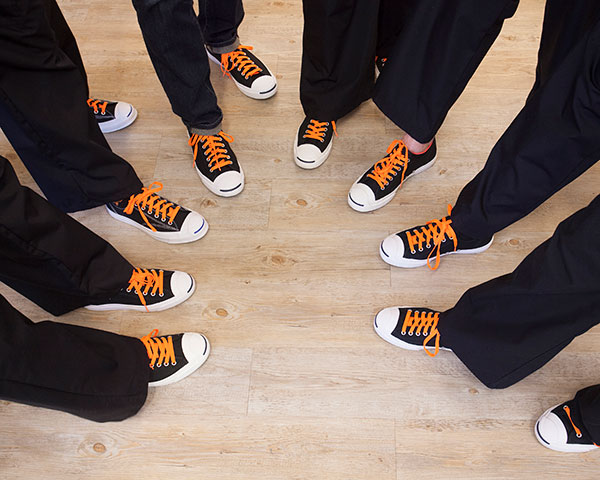 Closeup of dental team's black and orange shoes at orthodontist office in Salem, OR.